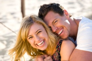 Happy couple embracing and laughing on the beach